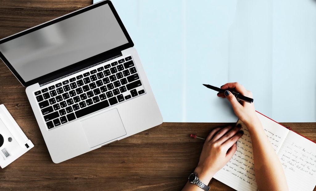 Escritura a mano frente al teclado de un portátil.
